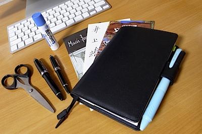ほぼ日手帳と、万年筆と、パンフレットと、のりと、ハサミの写真
